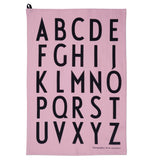 A light pink cotton rectangle printed with a bold black alphabet.