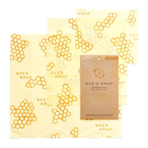 Three yellow honey comb pattern sheets are laid out showing the different sizes. A natural cardboard color Bee's Wrap packet sits on top.