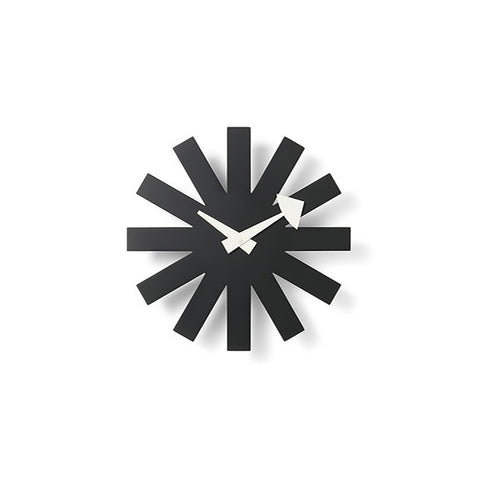 Wall clock designed from a flat black metal sheet as a minimalist snowflake with twelve rays. Two flat white hands at the center.