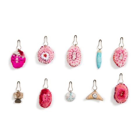 Recycled Jamdani Amulet showing two rows of five variously shaped amulets in pink, rose, turquoise and neutral tones made from repurposed fabric, cotton, silk embroidery and metal attachers.
