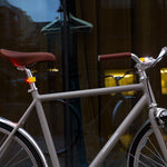 A pair of yellow bike lights fastened to the front and rear of a light gray bike with tanned brown seats and handles.
