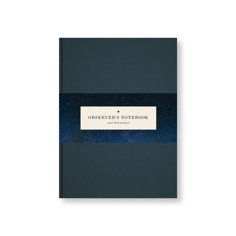 Deep blue canvas covered notebook with belly band featuring title in a vintage font surrounded by a photo of a deep starry night sky