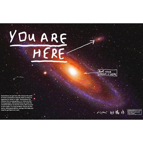 "A poster featuring an image of the milky way. White text reads ""You are Here"" with an arrowing pointing to one area of the image. White text reading ""But your dream is here"" with an arrow pointing to a different spot."