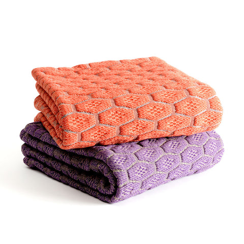 A pair of orange and purple throw towels stacked up.