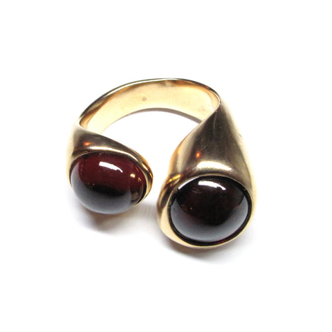 A wide band bronze ring with double stone top. The stones on the ring are round pieces of Garnet. The dark red stones are set into the bronze and are separated by an opening, allowing the wearing to stack additional rings on one finger.