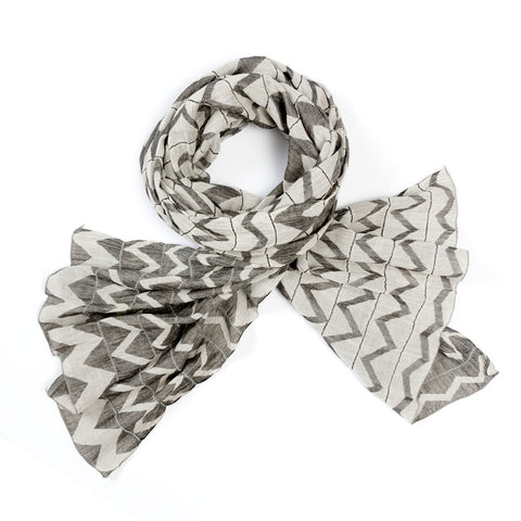 Gray and white reversible scarf with horizontal bands of contrasting zig zag stripes divided by single rows of parallel  stitching, displayed in a loop with splayed ends.