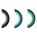 Three trivets in there collapsed state, resembling a rainbows' arch, placed horizontally against a white surface. Each trivet forms a gradient of 3 colors. The trivets are in shades of gray, blue, and green.
