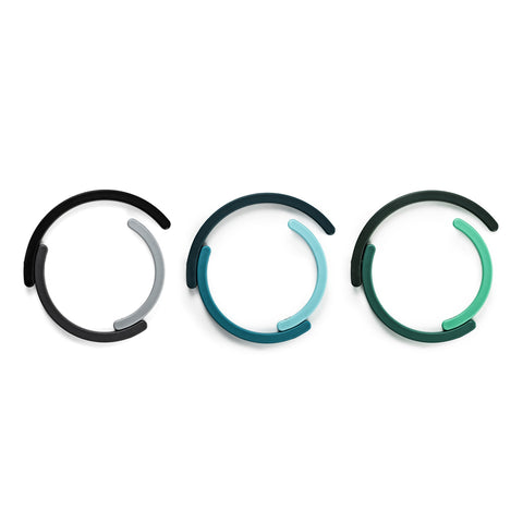 Three collapsible plastic trivets in shades of gray, blue, and green placed horizontally against a white surface.