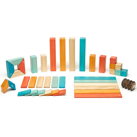 An entire set of 42 wood Tegu pieces laid out and grouped by shape.  The Sunset color pieces include turquoise, cream, yellow and orange.