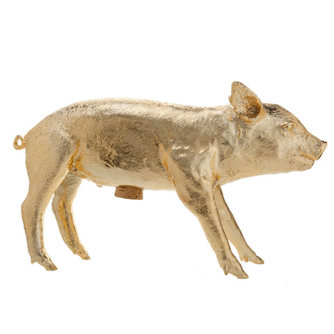 Side view of gold colored bank in the form of a young piglet with cork stopper at its belly, shot on a white background.