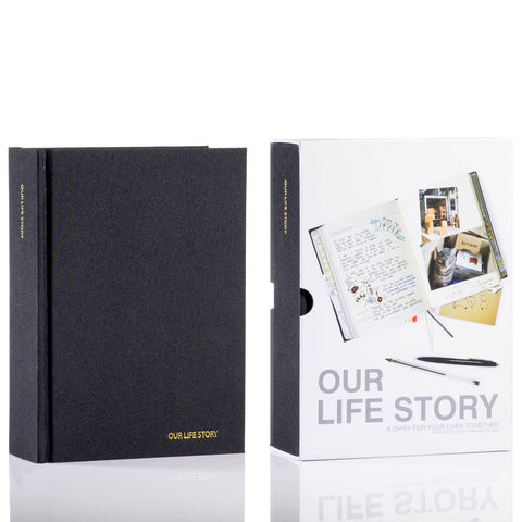 "Journal with a black cover shown inside and outside its sleeve. At the bottom right corner, ""OUR LIFE STORY"" is embossed in gold."