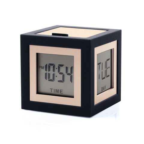 Black cube with small displays on each face, screen is framed in a narrow gold frame. Two visible screens display the date and day of the week.