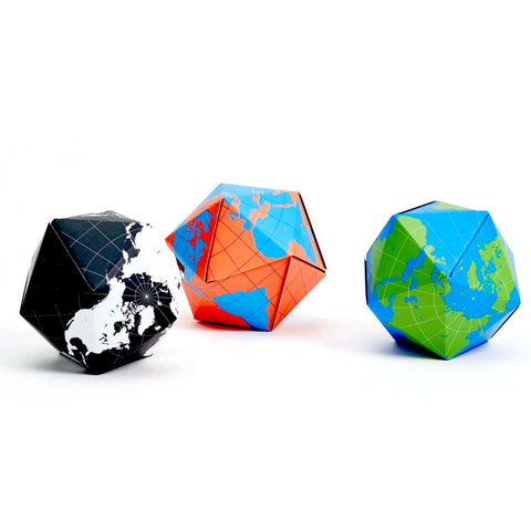 A photograph of three different color variations of the folding globe; black and white, orange and blue, blue and green.