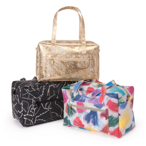 Three translucent small duffle bags. Each detailing a different scrap fabric including silk tassel, gold fringe, and yarn