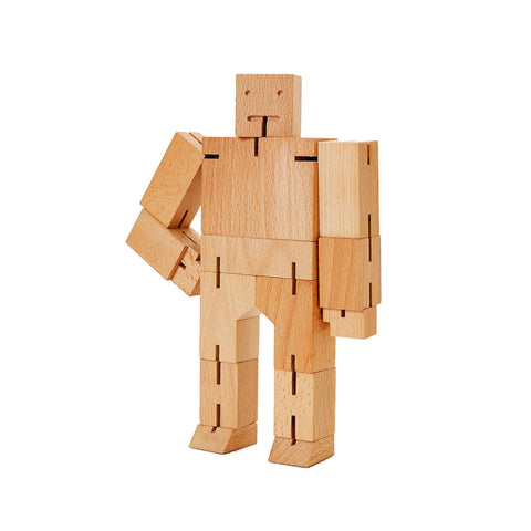 Medium Cubebot in natural wood in standing position with right arm bent on hip.