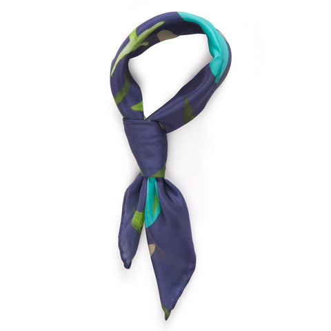 A navy blue silk scarf  with soft shapes in blue and green painted across its center. The scarf is styles in a knot suggesting a way to wear it.