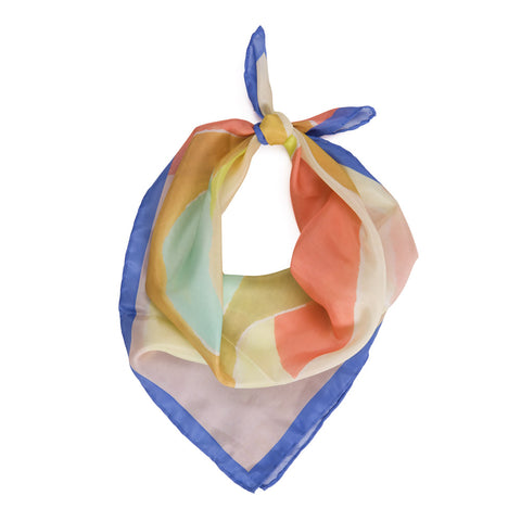 A blush colored scarf with blue trim. A series of shapes are painted in the center in various pastel colors that include a sea foam green, coral, and light yellow. The scarf is tied into a knot at the top in a suggestive style for wearing out.