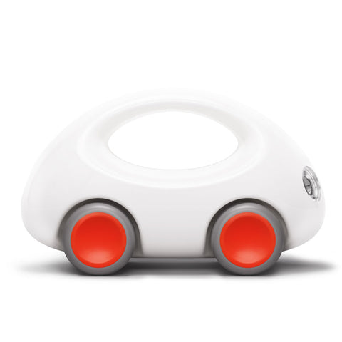 A small white toy car with rounded edges and a built in handle for ease of use. Its wheels are a bright red with gray trim.