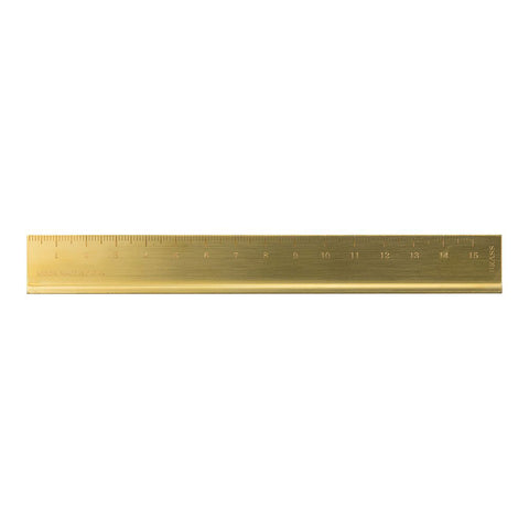 Image of a brass ruler sitting horizontally. The measurements are engraved across the top edge from 1 to 15. The bottom edge has a raised lip.