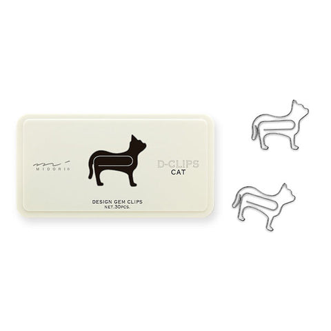 White container with black cat image on front. Two cat-shaped metal silver paper clips lay flat next to container..