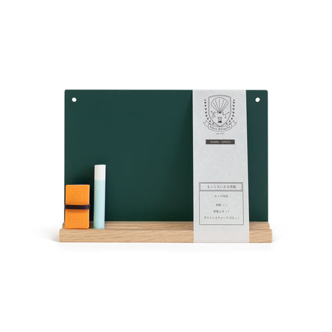 An image of a green mini chalkboard sitting upright on a wooden stand.  Two square orange erasers and a piece of chalk sit on the left side and a paper band with company logo wraps vertically around the board on the right. Punched out on the top left and right corners of the board are small holes for hanging.