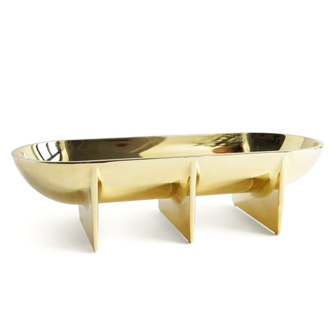 An elongated oval brass plated bowl mounted on three planer style legs. The brass coating is shiny and reflective.