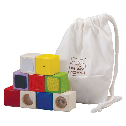 9 small wooden blocks and six different colors. Each block has a sensory function to teach babies about their senses. The blocks come inside of a cotton carrying case with drawstring closure.
