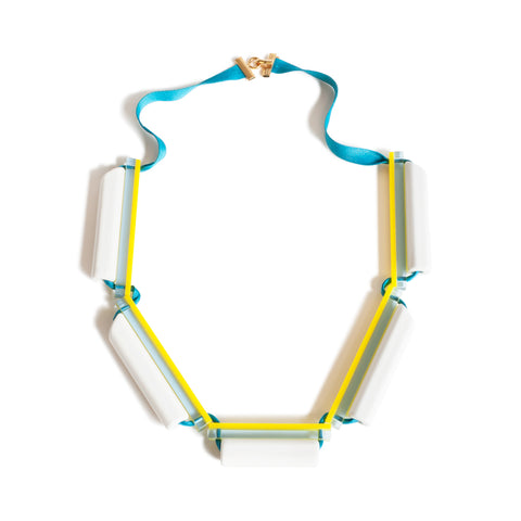 This necklace is designed from five acrylic modules with white, clear, and yellow stripes. Assembled together by a blue ribbon with a golden clasp on the back.