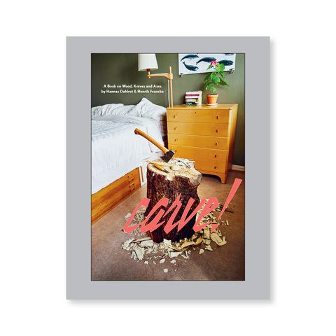 Gray book cover with a photograph of a tree stump with an ax and other tools on it in a carpeted bedroom
