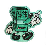 "A stack of dollar bills in the form of a whimsical green cartoon character. Its eyes are dollar signs and ""Good Luck"" is sewn across the feet."