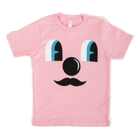 Light pink t-shirt with cartoon face. Two eyes, blue look off to the side, a circular nose and mustache with no mouth