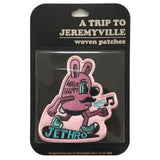"A blister pack with a Jethro walking patch inside. Brand logo, ""A Trip to Jeremyville"" is embossed at the top."