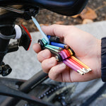 Close-up of a light skinned person's hand holding the Rainbow Multi Tool Set with the light blue Allen key extended to make adjustments to a black bicycle seat.