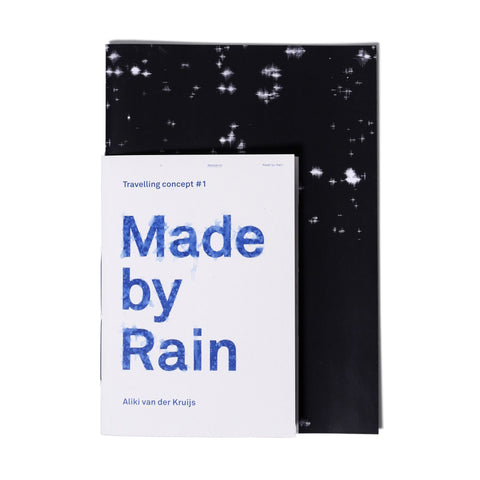 Made by Rain Book; black cover with a few small splashes of white and smaller off-white booklet layered over, with the title in blue [traveling concept #1 booklet]