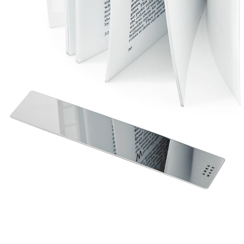 A photograph of a Mirror Bookmark laying flat adjacent to a book. The pages of the book are reflected on the bookmark. The Areaware logo is visible from this side, and sits at the bottom end of the bookmarl.