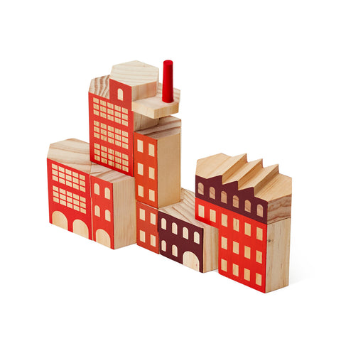 Against a white background, a photograph of a factory block set assembled and shown on an angle. The wooden blocks are painted red and burgandy and are assembled together into one large building. Different hexagonal shapes fit together to make the larger more complex structure.