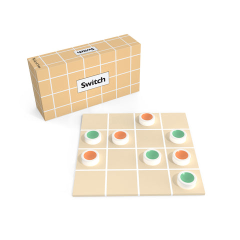 "A game in play on a tan square board with a white 4 by 4 grid printed on it. Eight, white, disk-shaped games pieces with colored depressions on the top in either orange or green each sit in their own grid square. The game box with the same pattern as the board and text ""Switch"" sits in back."
