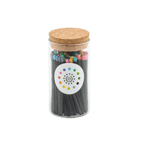 Frontal view of small glass container full of black matches with multicolored tips, and cork top piece