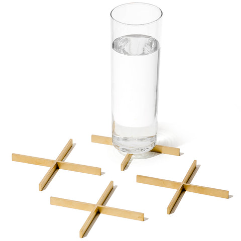 Four brass X-shaped coasters. A glass of water has been placed onto one of the coasters.