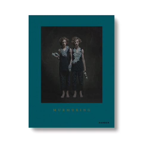 Teal book cover with photograph of long haired light skinned twins wearing black pants and tops and highly textured oversized jewelry peices around their necks and hands. Title in gold font at the bottom in serif font