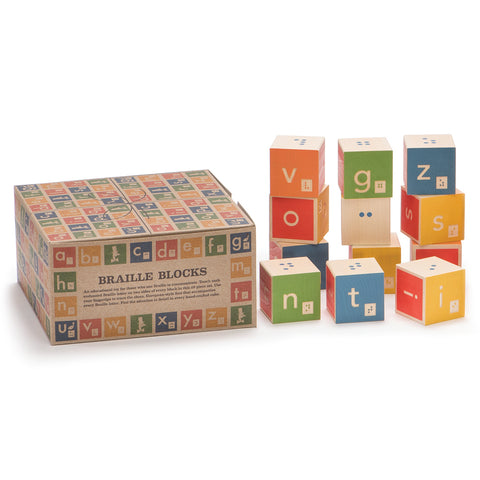 A set of 12 multi-colored  building blocks are loosely arranged in three stacks. Some blocks have the font side showing while other blocks have the braille side visible. The game box sits closed next to the stacks. It is a natural cardboard color and is decorated in colorful illustrations of blocks.