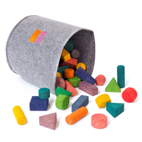 A large grey felt bucket is tipped on its side with cork building blocks tumbling out.  Blocks are multi-colored and multi-shaped. The pink and orange KORXX logo is sewn on the bucket.