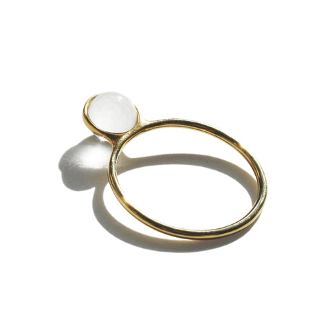 Gold ring with white stone.