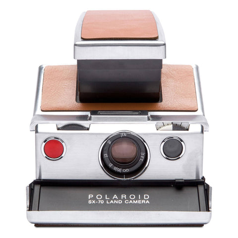 Polaroid SX-70 Refurbished Camera from the front. Brown leather top, metallic corpus.