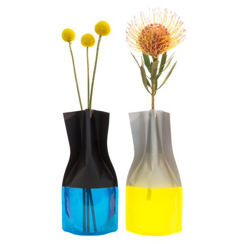 Two tall wine bottle shaped flower vases that are made out of plastic. Both vases are two-toned with a translucent base and opaque top.