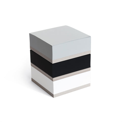 A three quarter view of  the tri-color Ito Bindery Small Memoblock on a white background; three individual memo pad squares in white, black and gray, with thick recycled cardboard bottoms stacked vertically.