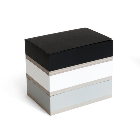 A three quarter view of  the tri-color Ito Bindery Medium Memoblock on a white background; a vertical stack of three individual memo pad rectangles in white, black and gray, with thick recycled cardboard bottoms.