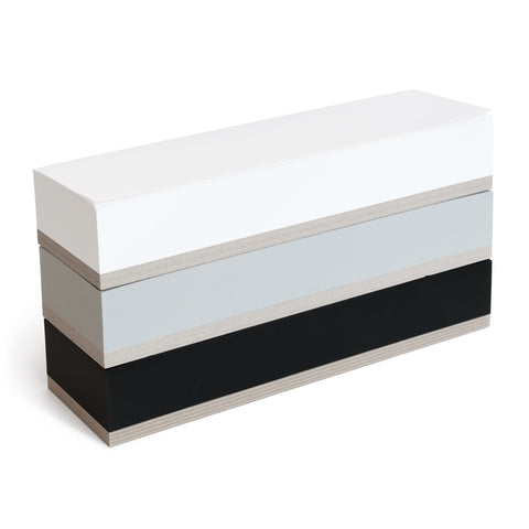 A three quarter view of  the tri-color Ito Bindery Large Memoblock on a white background; a vertical stack of three oblong individual memo pads in white, black and gray, with pristine surfaces, crisp edges and thick recycled cardboard bottoms.