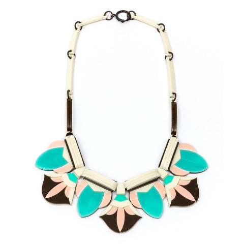 Acrylic necklace assembled from numerous black, light pink, turquoise, and white elements that form a floral motif.