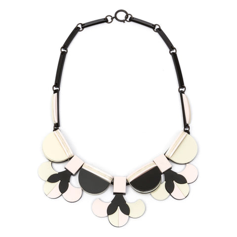 Acrylic necklace assembled from numerous black, light pink, and white elements. Three flowers at the center attached to semicircular shapes.